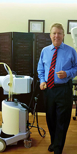 Dr. Robert Kuske and a brachytherapy device
